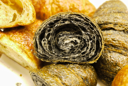 Cross section showing structure of delicious and buttery Charcoal Croissants made by pastry chef. All look very tasty and delightful. Natural light. Close up.