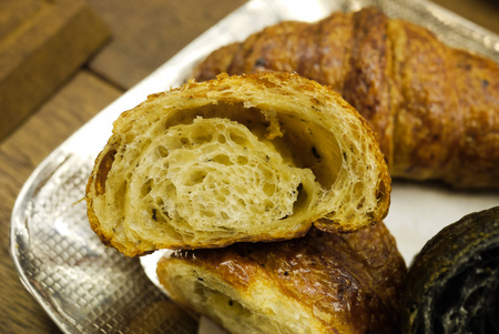 Cross section showing structure of delicious and buttery Truffle Croissants made by pastry chef. All look very tasty and delightful. Natural light. Close up. Imagens