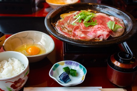 Set of tasty and delicious Japanese Sukiyaki nabe with best-quality cuts of thinly sliced sirloin or rib eye or tenderloin Kuroge Wagyu beef in a cast iron pan. Good Marble Score. Natural light.