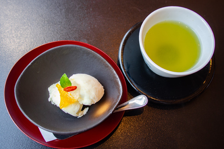 Aromatic, tasty and delicious Japanese Yuzu Citrus sorbet ice cream garnished with Yuzu Marmalade or sweet preserved zest and Goji berry. Serve with green tea. Healthy eating concept. Natural light.