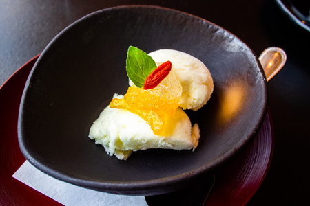 Aromatic, tasty and delicious Japanese Yuzu Citrus sorbet ice cream garnished with Yuzu Marmalade or sweet preserved zest and Goji berry. Close up. Healthy eating concept. Natural light. Stock Photo
