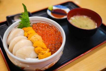 Tasty and delicious Sushi Donburi or Japanese rice bowl topped with fresh Sashimi Hotate(scallop),Ikura(salmon roe) and Uni(Sea Urchin) with Wasabi at a restaurant. Healthy Eating and Eat Well Concept Фото со стока