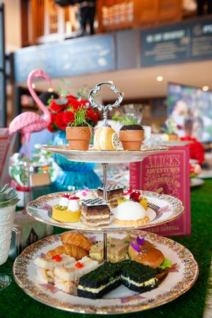 Magical and colorful set of afternoon tea in Alice in Wonderland theme. Tasty and delicious dessert, savories, bakery and pastry. Good for high tea party or Birthday celebration. Natural light.