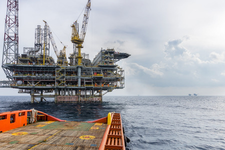 starboard: A boat sail away from offshore oil rig Editorial