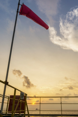 weather gauge: Windsock and communication dome on the construction barge during sunrise at oilfield Malaysia