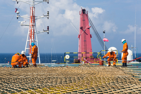 helideck: Offshore construction crew installing helideck netting on construction barge at oilfield Malaysia