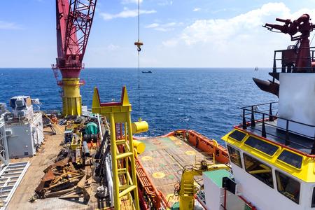 handling: A tug boat alongside construction barge performing anchor handling at oilfield Malaysia