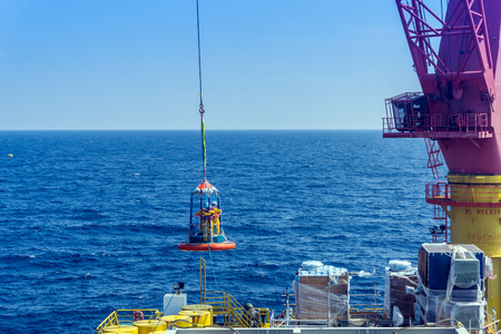 Offshore worker being transferred with personal transfer basket from tug boat to construction barge using crane