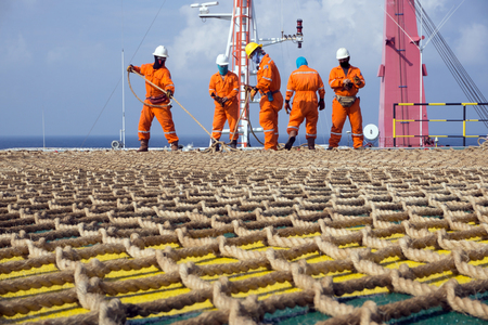 helideck: Offshore workers working on the helideck of a construction barge in oilfield Malaysia