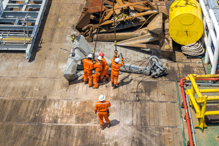 rigger: Offshore workers handling anchor to be lifted for deployment on construction barge at offshore Terengganu, Malaysia
