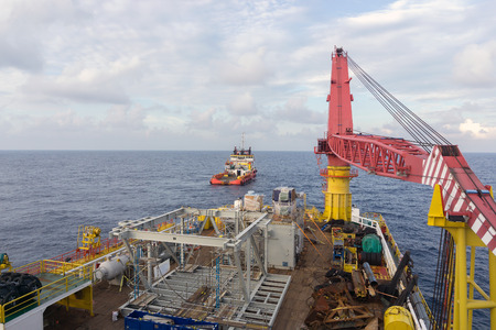 handling: Deck view of construction barge with anchor handling tug in the background