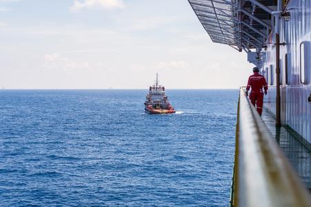 handling: Offshore worker walking on the walkaway on board construction barge monitoring anchor handling operation at Terengganu oilfield, Malaysia Editorial