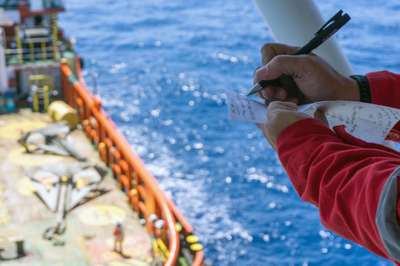 handling: Offshore worker taking note while performing anchor handling operation at Terengganu oilfield, Malaysia