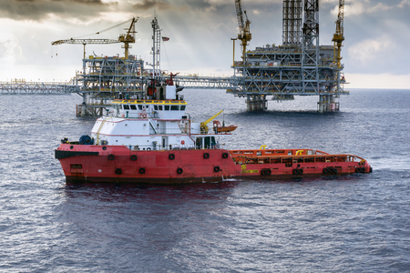 buoys: Anchor handling tug approaching oil rig or platform during anchor handling operations Editorial