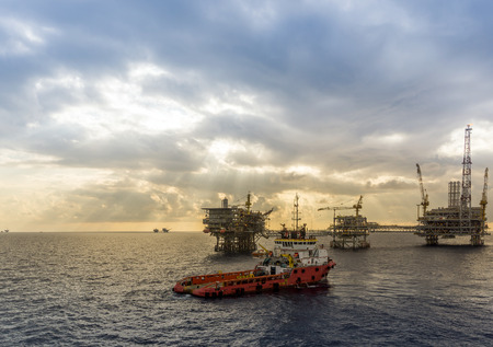 handling: Anchor handling tug approaching oil rig or platform during anchor handling operations Stock Photo