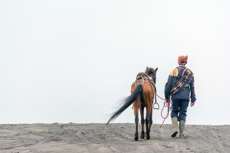 Mt. Bromo , Indonesia. May 21, 2016. A horseman walking his horse on sand dune after providing horseback riding services to tourist at Bromo-Tengger-Semeru National Park, a nature reserve. Editorial
