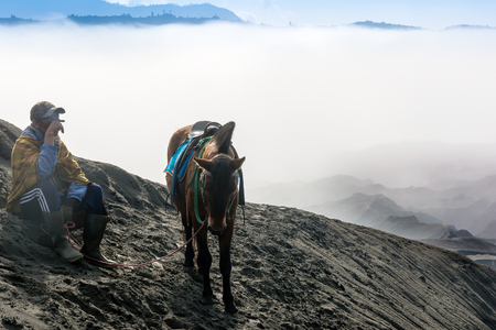 horseman: Mt Bromo, Indonesia. May 21, 2016. A horseman taking rest on top of sand dune at Mount Bromo of Bromo-Tengger-Semeru National Park, a protected nature reserve since 1919.