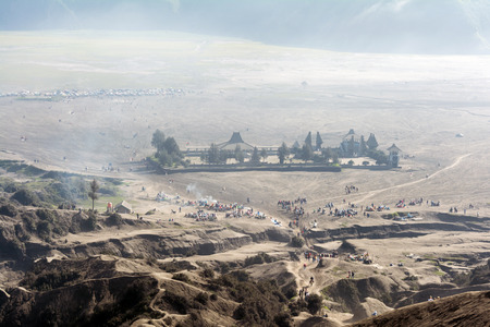 Looking down at the misty morning of sea-sand caldera plain from Mount Bromo. Tourists can be seen flocking around taking selfie, strolling, walking and horseback riding along the path.