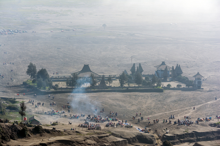 flocking: Looking down at the misty morning of sea-sand caldera plain from Mount Bromo. Tourists can be seen flocking around taking selfie, strolling, walking and horseback riding along the path.