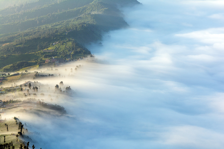 A layer of fog or mist covering the village of Cemoro Lawang in the morning at Bromo-Tengger-Semeru National Park, East Java, Indonesia