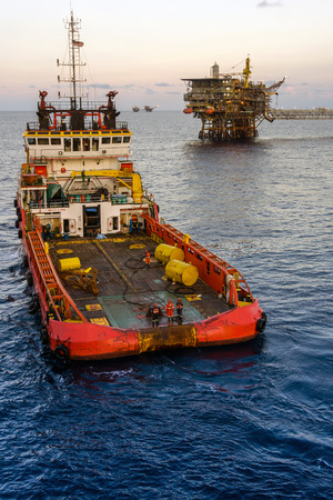 Anchor handling tugboat at offshore oilfield complex platforms