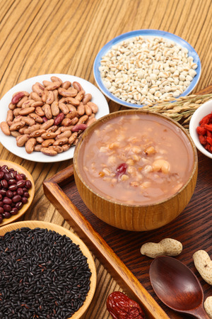 Congee with Nuts and Dried Fruits on wooden background