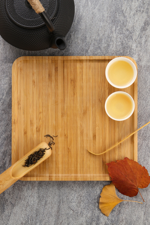 Tea set on a wooden plate on cement background