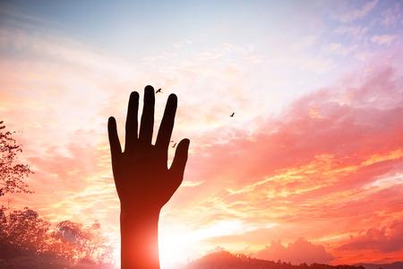 Lobpreis- und Anbetungskonzept: Hand der christlichen Leute des Schattenbildes, die über unscharfes Kreuz auf geistigem hellem Hintergrund steigt