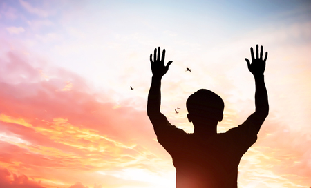 praise and worship concept: Silhouette christian people hand rising over blurred cross on spiritual light background