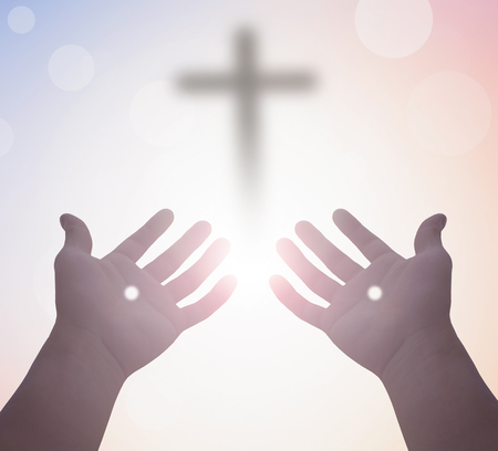 Concept of resurrection of Christ Jesus: hands with nails on the background of the cross