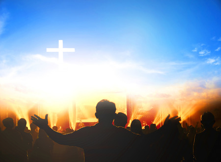 Church worship concept:Silhouette of Christian prayers raising hand while praying to the Jesus Editoriali