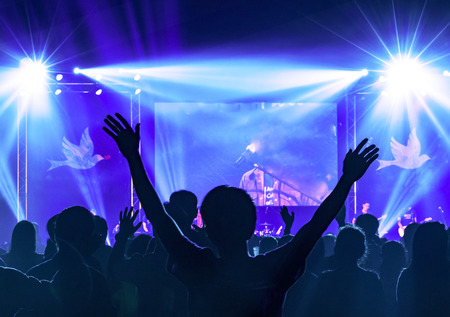 Silhouette of many people raised hands in a concert
