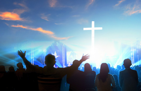 Worship and praise concept: Silhouette many people raised hands over sunset background Sajtókép