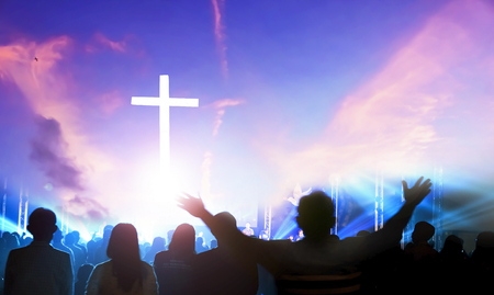 Worship and praise concept: Silhouette many people raised hands over sunset background Редакционное