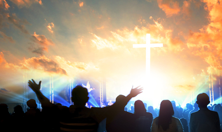 Worship and praise concept: Silhouette many people raised hands over sunset background Redactioneel