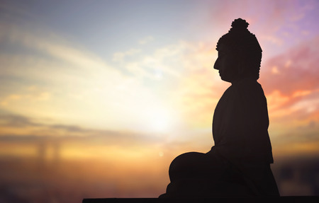 Silhouette of Buddha statue against sunset background