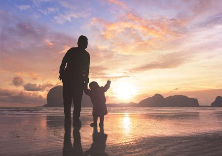 Concept de la fête des mères : maman et enfant sur fond de coucher de soleil Banque d'images