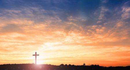 Black cross religion symbol silhouette in grass over sunset or sunrise sky