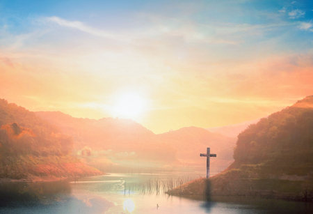 Surrender concept: Silhouette of crucifix cross on mountain at sunset time with holy and light background