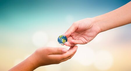 World Humanitarian Day concept: hands holding earth globe over natural background