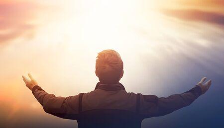 Concept de la Journée internationale de la paix : la silhouette de l'homme a levé les mains sur fond de coucher de soleil