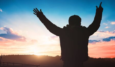 Human Rights Day concept: a man raising his hands over sunset background Standard-Bild