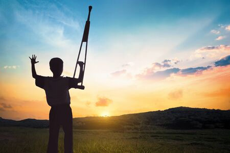 Concept de la Journée des droits de l'homme : homme handicapé levant ses béquilles au coucher du soleil
