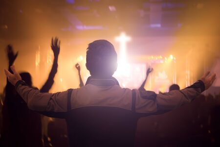 Worship concept: Christians raising hands in praise and worship night