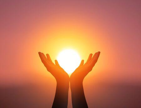 Concepto del Día Mundial de la Salud Mental: manos de oración de silueta en el fondo del cielo al atardecer Foto de archivo