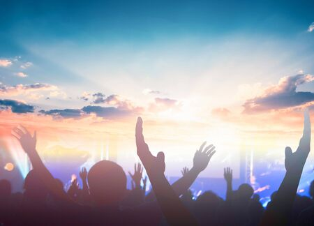 Worship and praise concept: christian people hand rising on sunset background