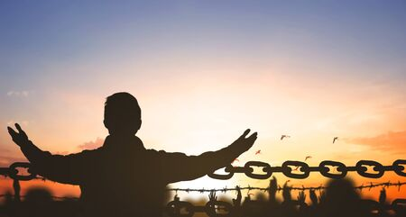 China Closed city concept: Silhouette refugee hands raising and barbed wire on sunset sky background