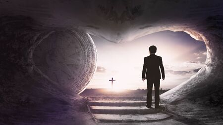 Easter Sunday concept: Tomb empty with cross on sunset background