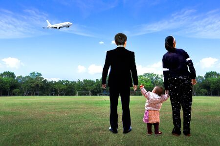 Global Day of Parents concept: Father, mother and child at Natural blue sky background