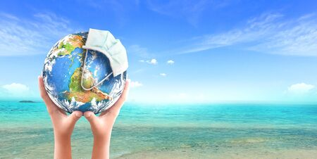 World Oceans Day concept: Abstract blurred background of ocean beach, Corona virus or COVID-19 Earth wearing a mask